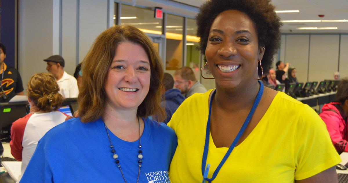 Henry Ford employees smiling in the Welcome Center with students enrolling or registering in the background