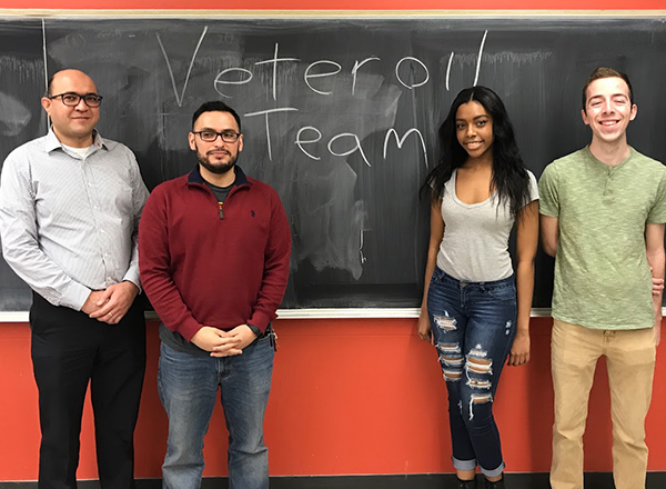 Breanna Allen in front of a chalkboard, with three men from the Engineering Club