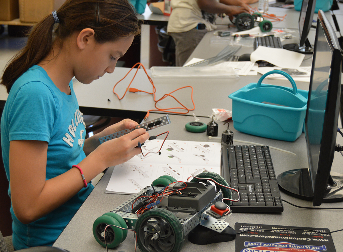 Young student assembling a small robot with wheels, sitting at a desk surrounded by small electronic parts