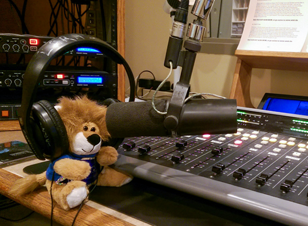 Small stuffed lion wearing headphones next to mixing interface in WHFR.fm studio