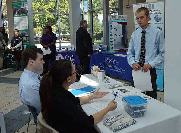 Employer speaking to two students at a table at an HFC career fair