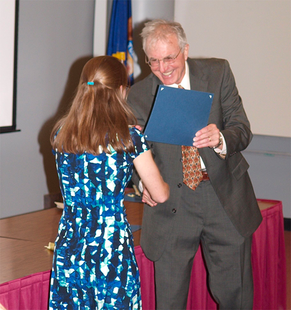 man handing award to woman