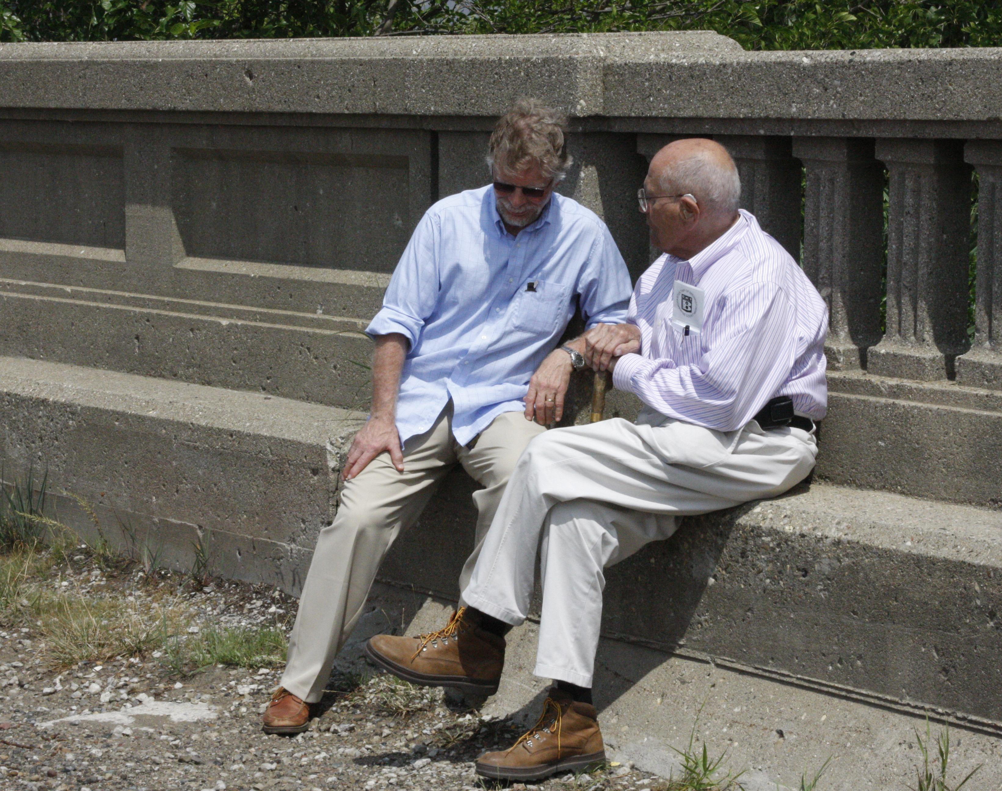 Daniel Harrison sitting on a bench talking to John Dingell