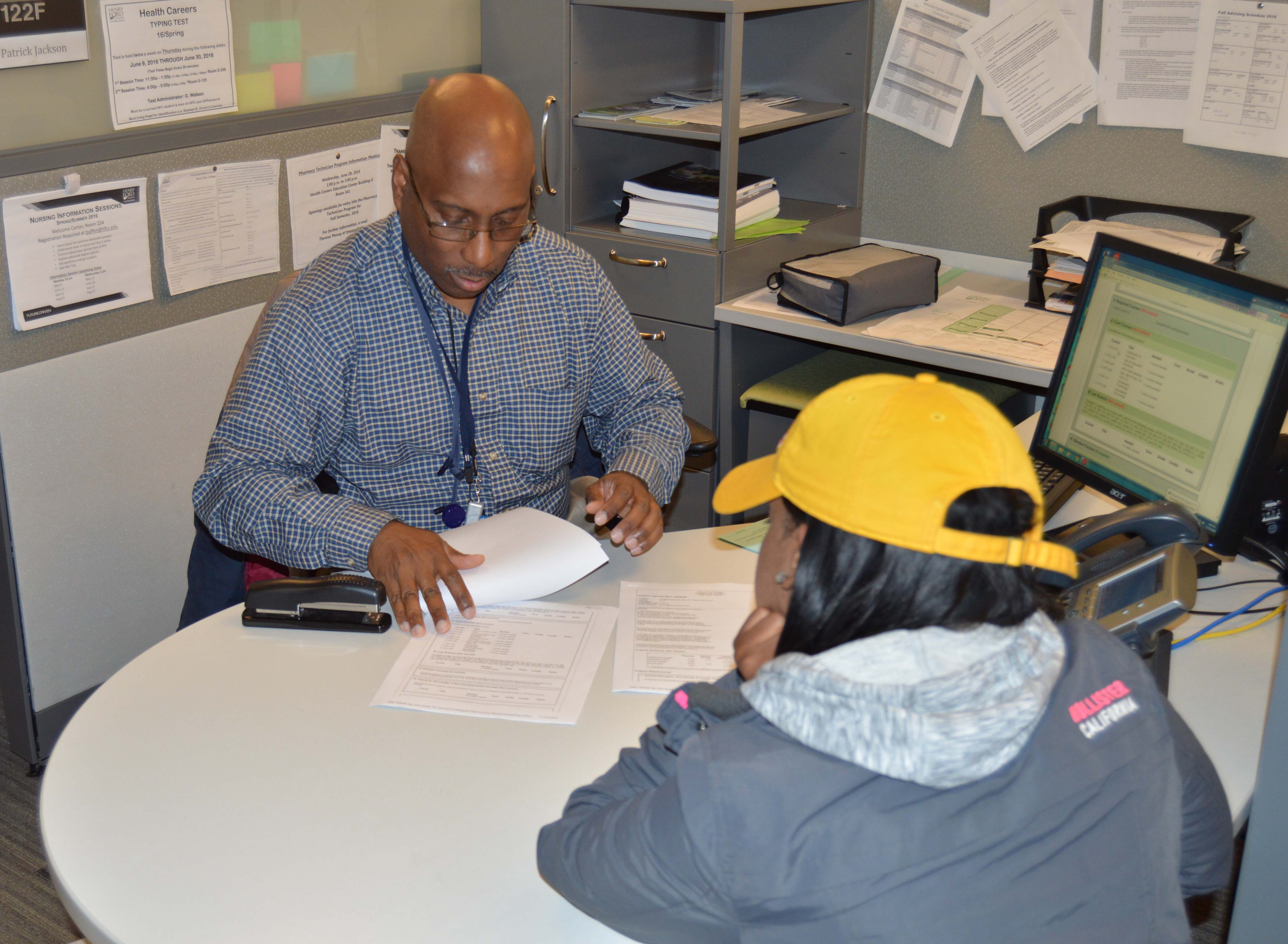 An advisor sits at desk with student, reviewing printed transcripts.