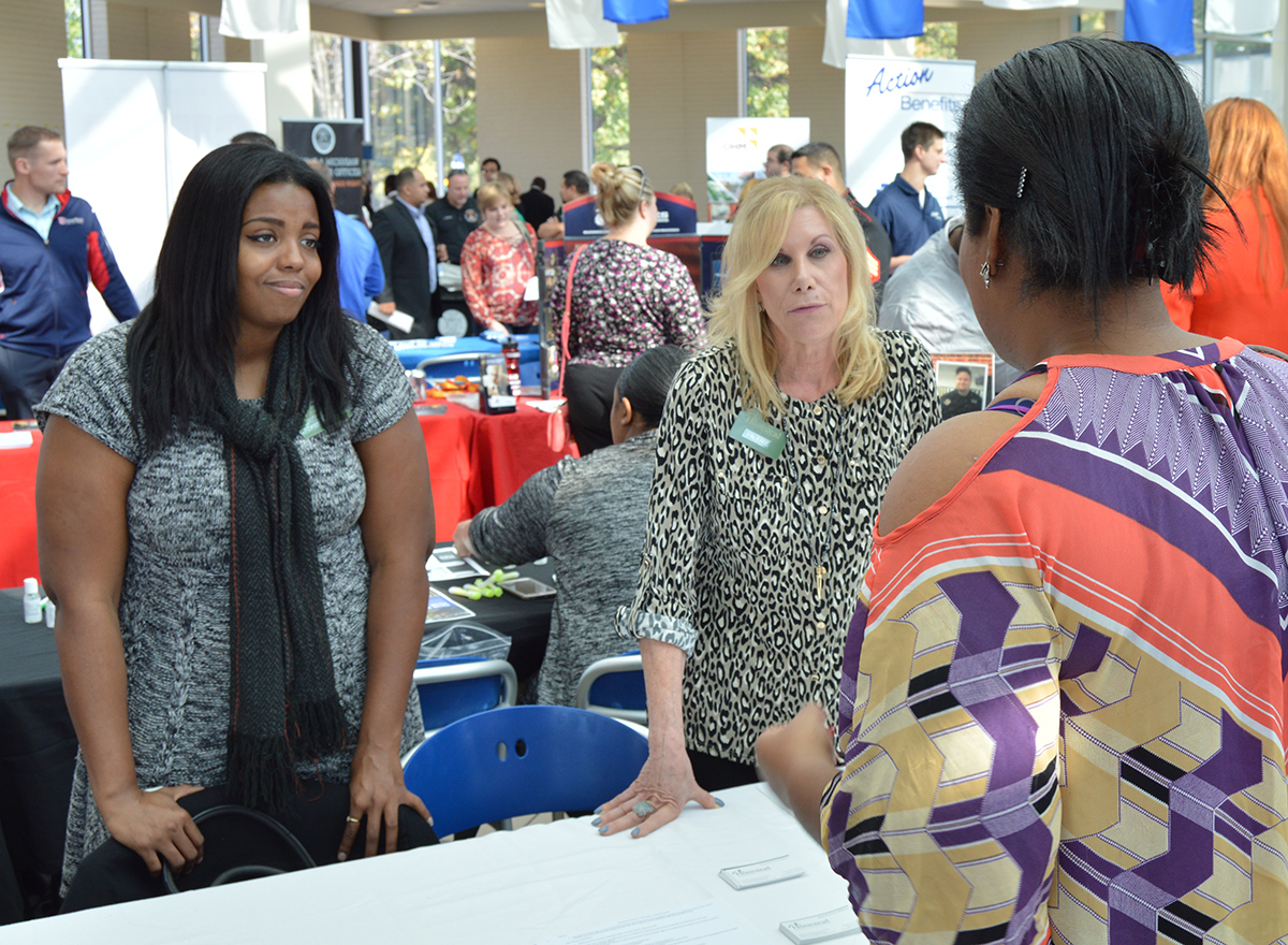 Two employers at the HFC Career Expo booth talk with a student.