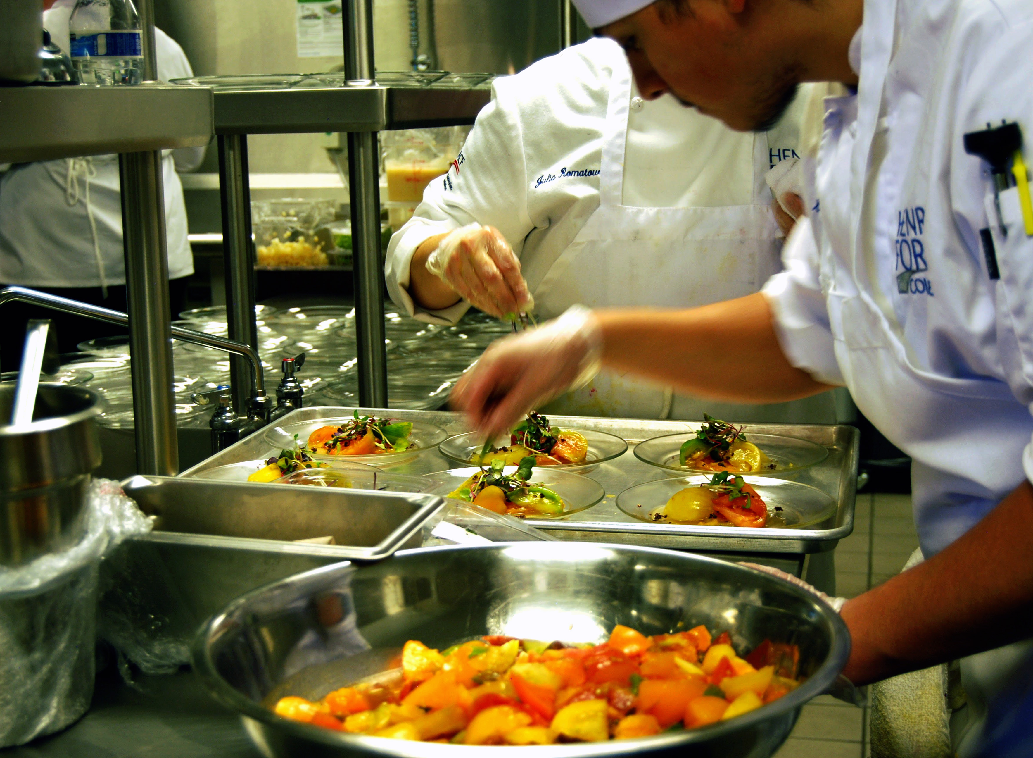 Culinary students putting garnishes on prepared dishes in an HFC kitchen