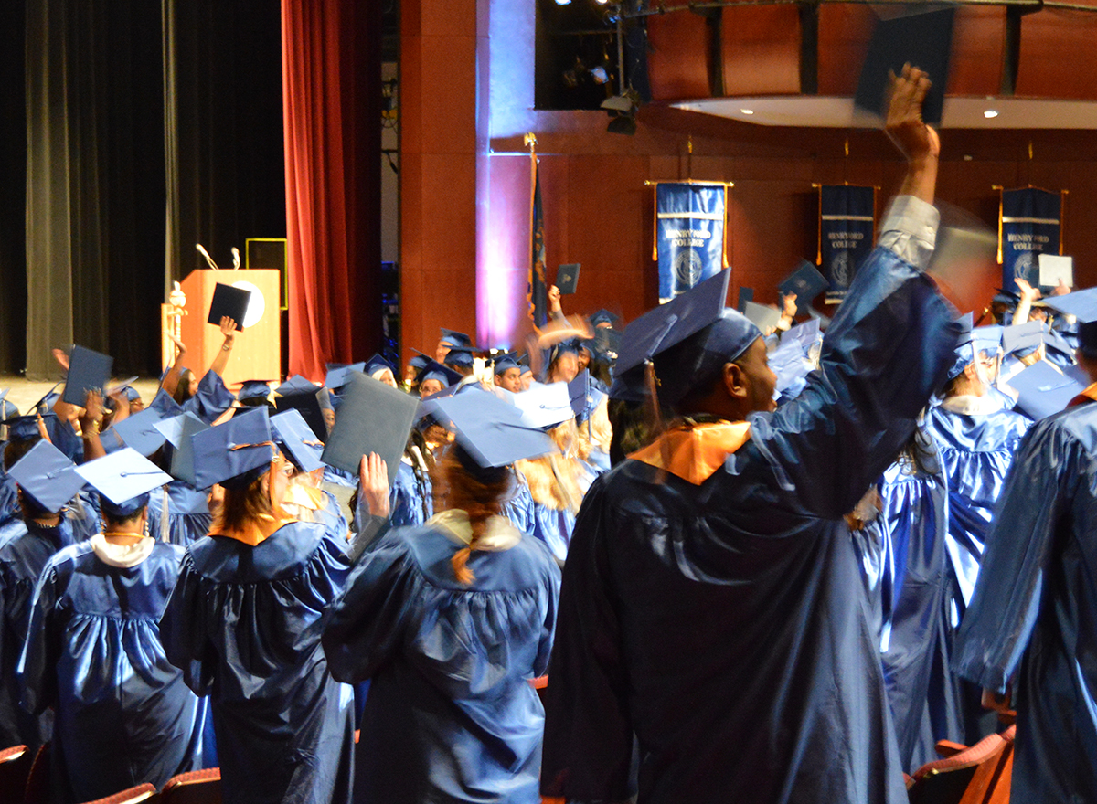 Numerous students wearing blue graduation gowns, some cheering and holding their caps up in the air