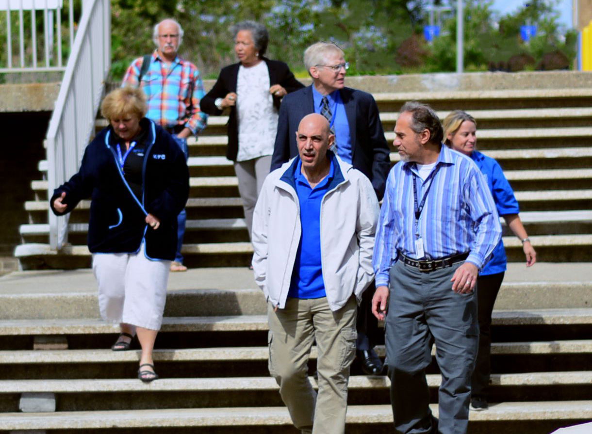 Henry Ford College Faculty and Staff walking down a flight of stairs outside, talking to each other