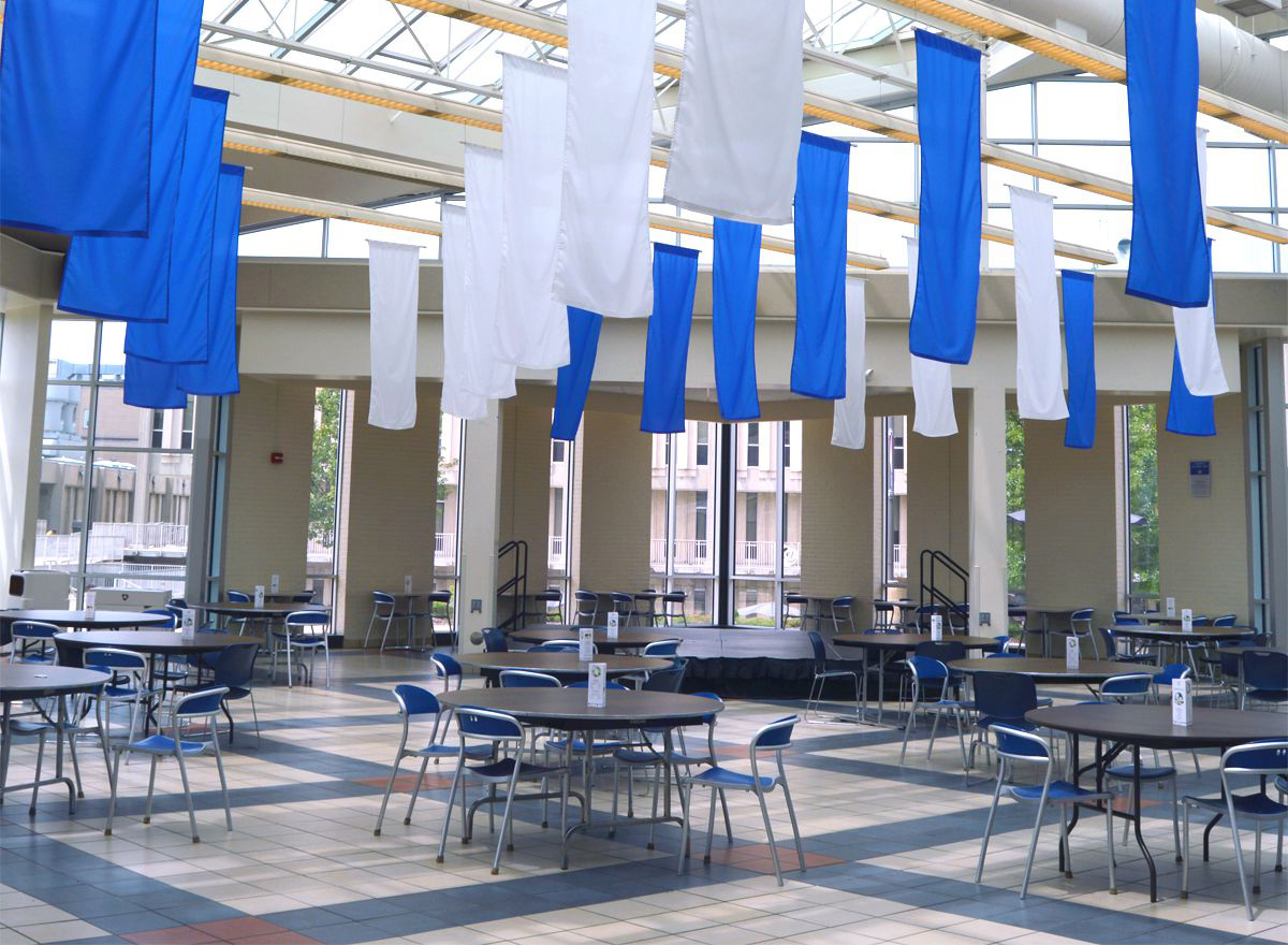 Student and Culinary Arts Center, with blue and white banners hanging from the ceiling and various tables with chairs lined up in rows