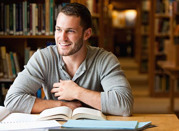 Smiling student sitting at library desk with open books