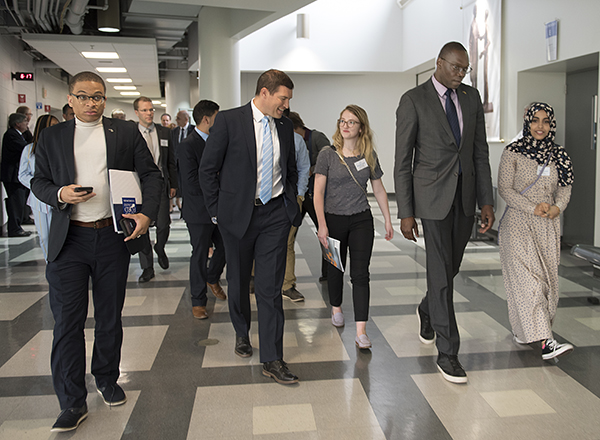 President Kavalhuna, Lt. Gov. Garlin Gilchrist, students and dignitaries walk to a robotics lab.