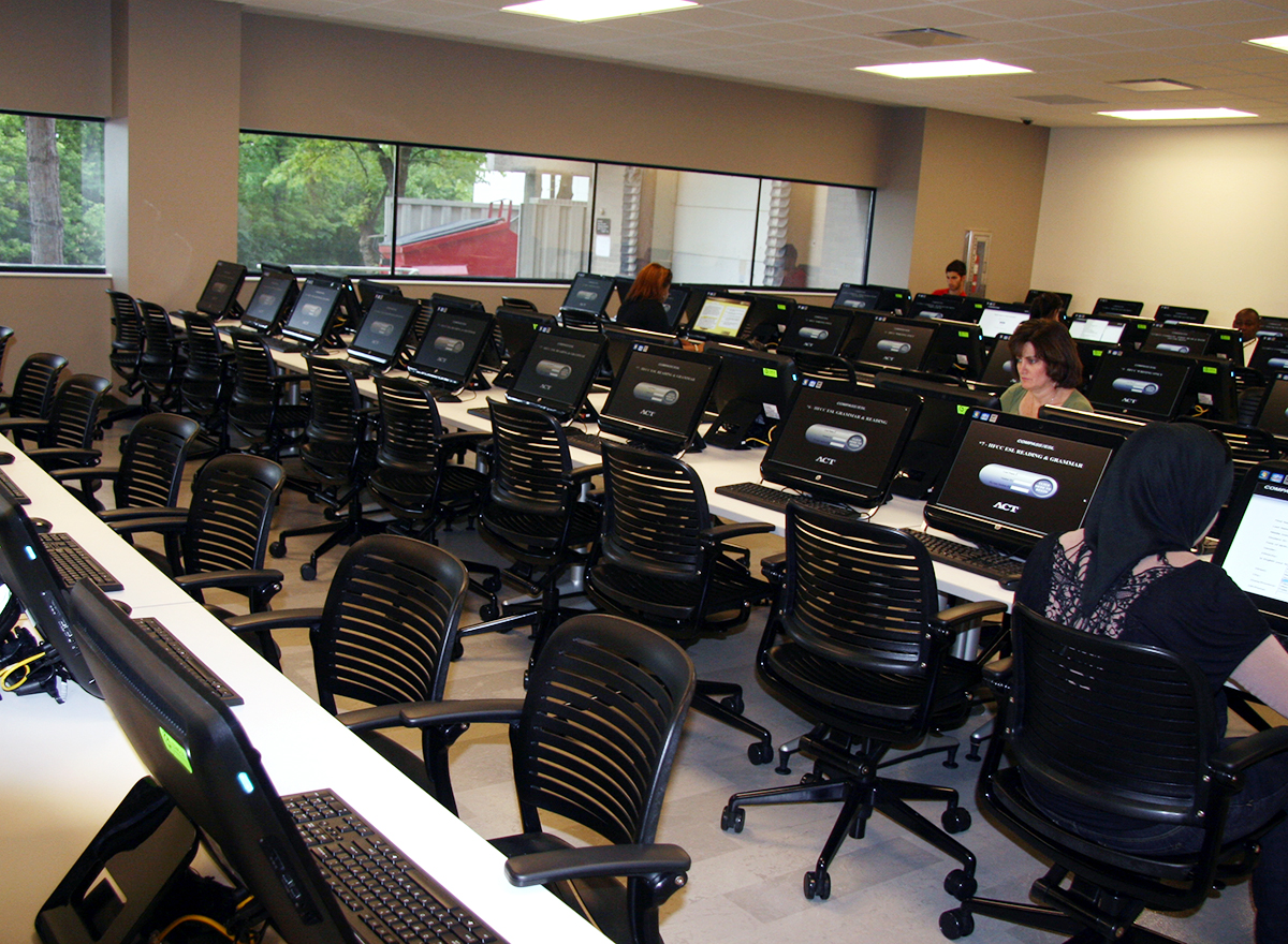 Students in the a computer lab with rows of workstations, participating in placement tests