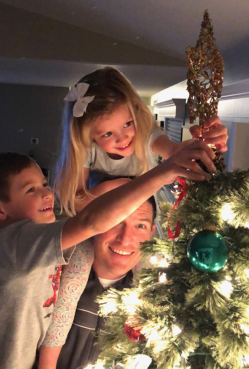 Russ with his children, trimming the tree.