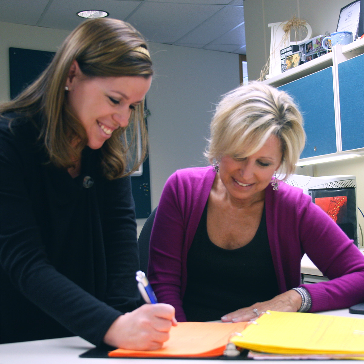 A staff member helping a student fill out paperwork