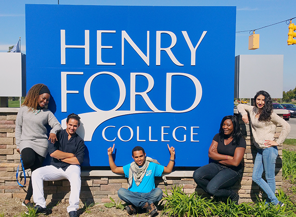students pose around large blue Henry Ford College sign