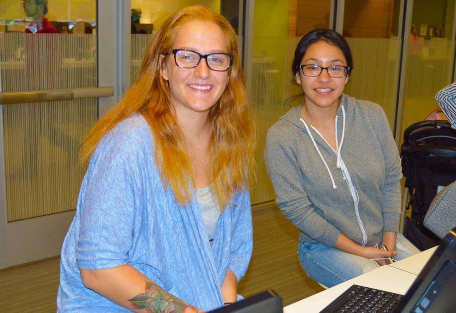 Two people sitting in the Welcome center at workstations smiling at the camera