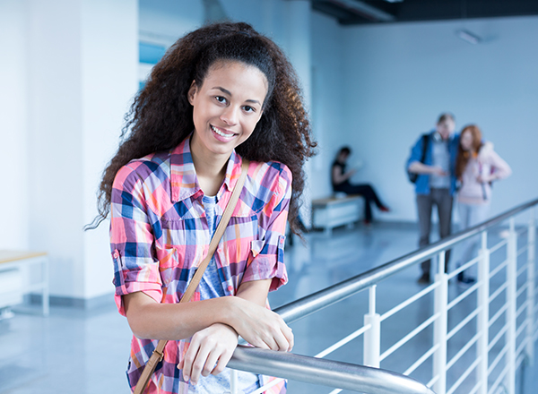 Student resting arm on railing, smiling and looking at viewer