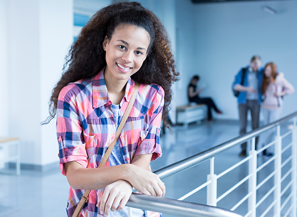 Female student smiling, leaning on railing