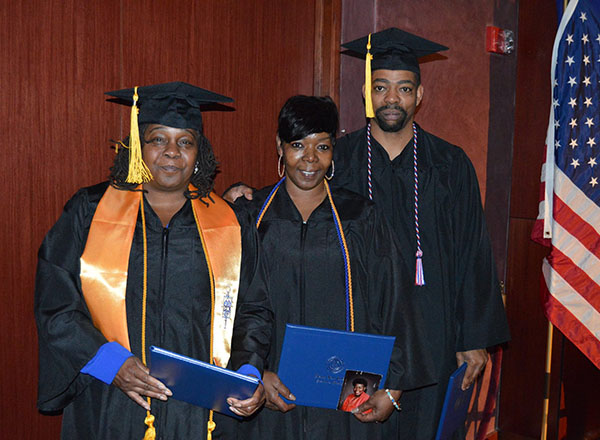 Three students at their commencement ceremony