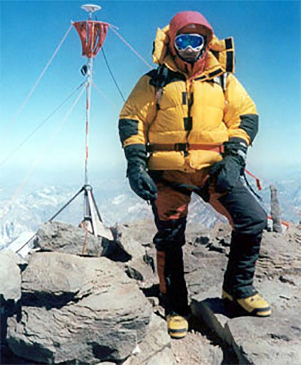 Man in mountain gear standing on summit.