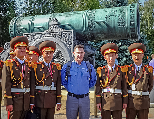 Four North Korean soldiers and one American civilian standing in front of a ceremonial cannon.