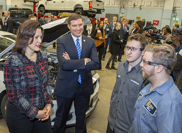 Governor Whitmer, President Kavalhuna, two students in auto lab