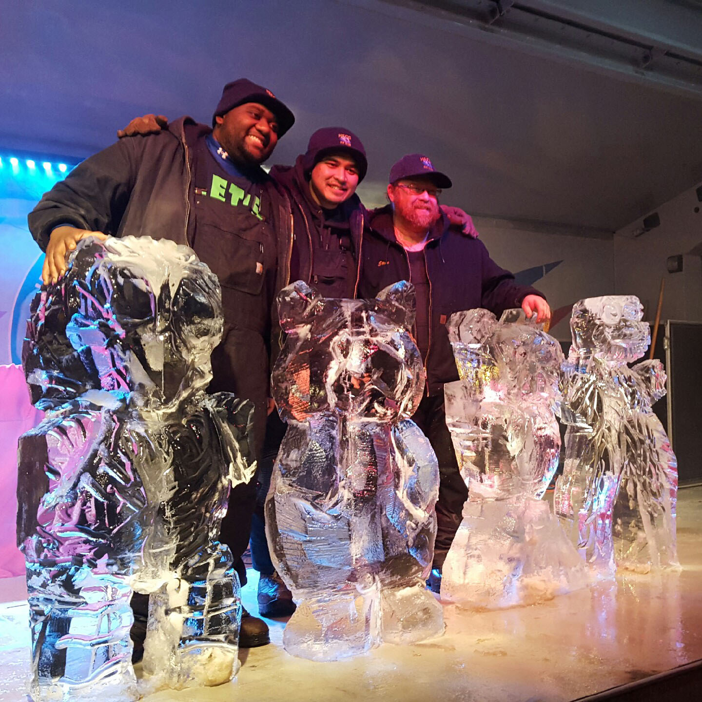 Students standing proudly behind ice sculptures on a stage in a competition