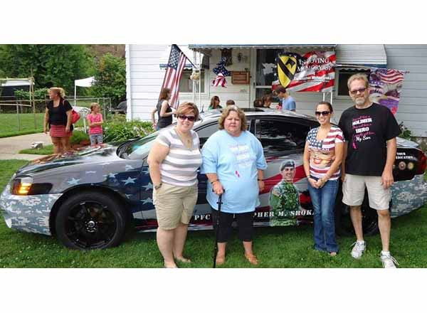 The family of the late PFC Christopher Sroka stand in front of the 2004 Grand Prix GTP that his father Mark restored to honor him. From left to right are Sroka's sister Lauren, mother Theresa, sister Samantha, and father Mark.
