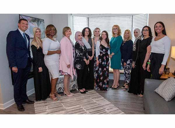 Karen Wilmering (fourth from left, dressed in pink) has been HFC's Interior Design program coordinator for 12 years. She's pictured here with President Russell Kavalhuna (left) and her students in the apartment home they redesigned at Henry Ford Village in Dearborn.