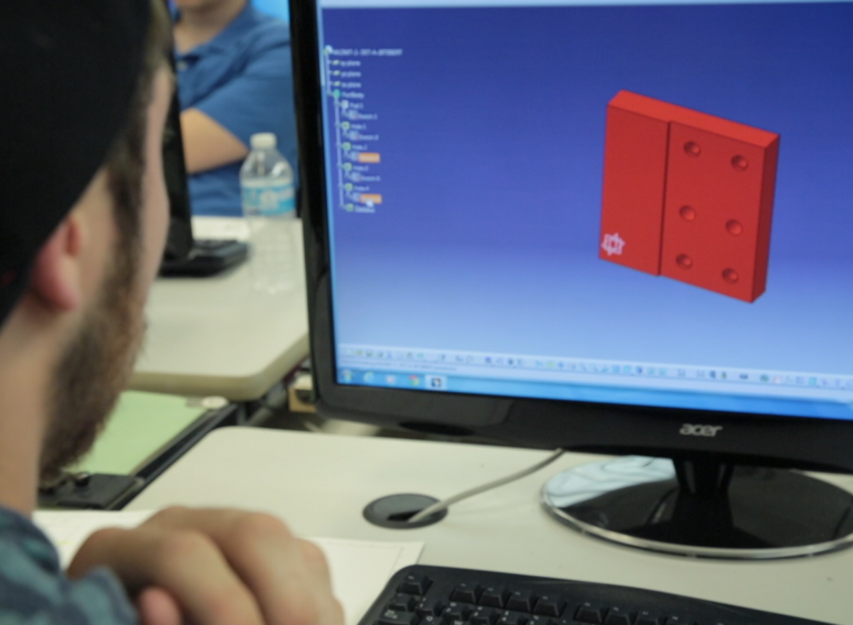 Closeup of a student sitting at a computer working on a red, square-shaped computer generated model