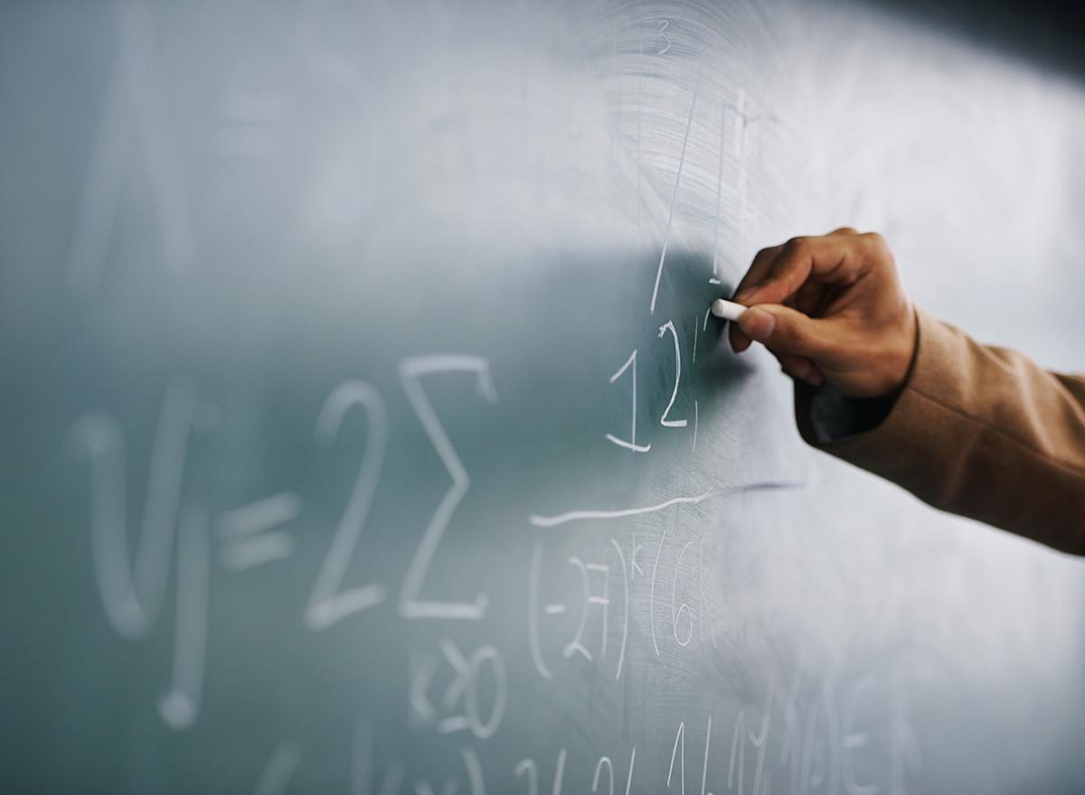 Hand writes math formulas on a green chalkboard with white chalk