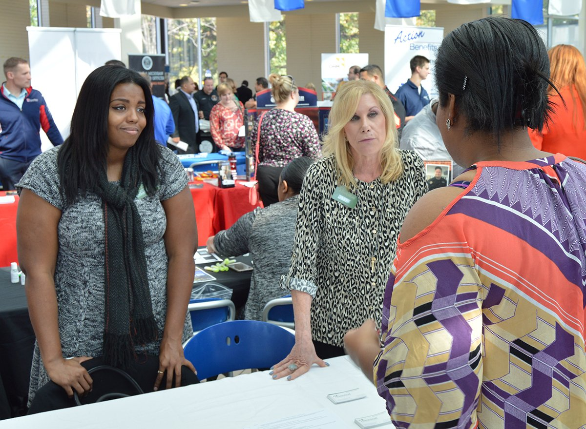 Woman at career fair talking to two employer representatives