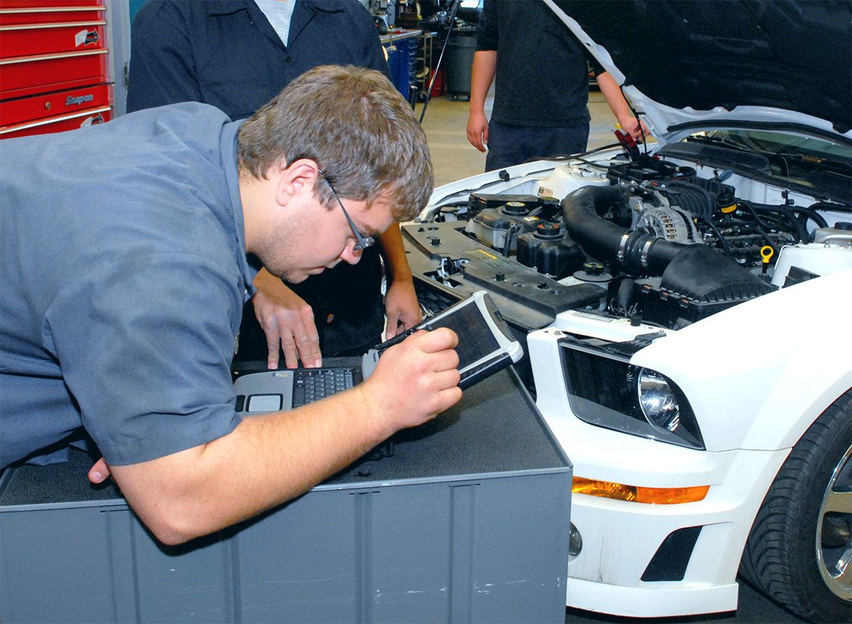 Student wearing safety glasses peering at a laptop computer screen for automotive diagnostics