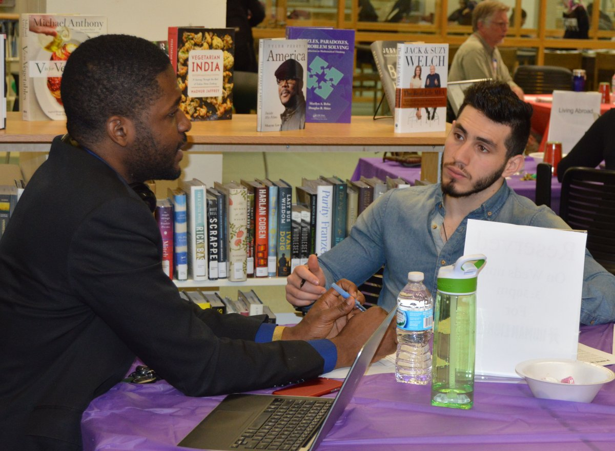 Two men sitting in a library at a round table, one of the men sitting in front of a laptop and the other gesturing and speaking