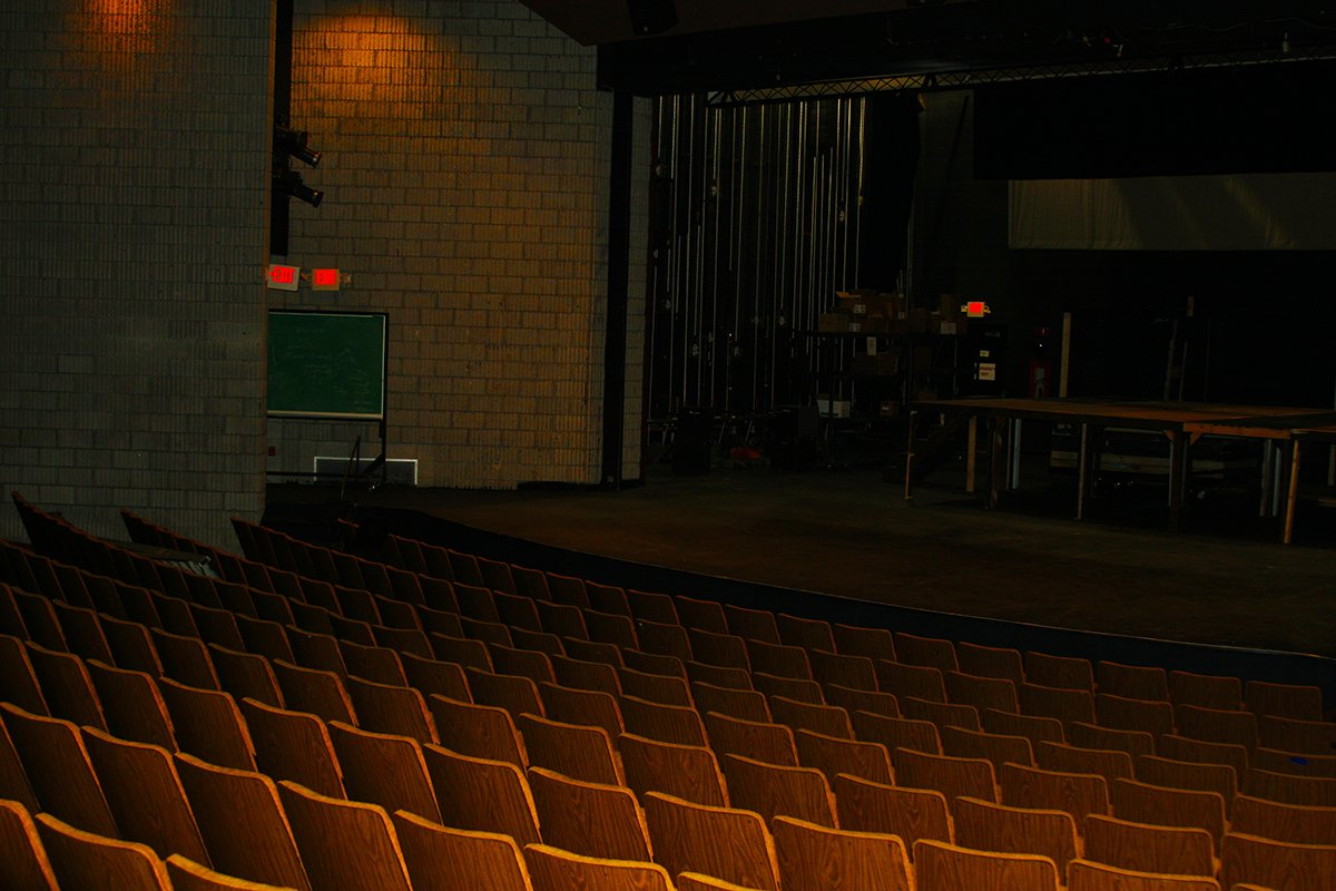 Photograph of inside of Adray Auditorium, with several rows of seats facing the stage that spans the width of the auditorium