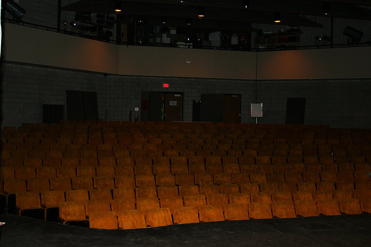 View of seats from an on-stage perspective, showing a top level where various theater equipment is used and maintained, and the sets of doors leading out of the auditorium on the main floor on the back wall, behind the seats