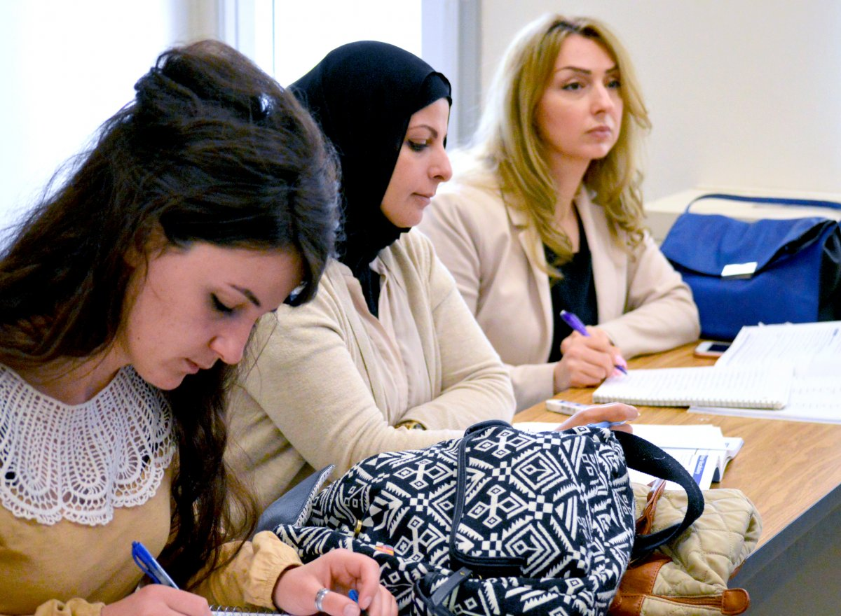 Three students listening to a lecture and taking notes