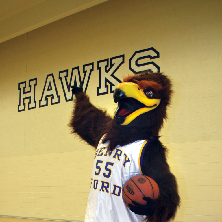 "HFC mascot hawk ""Hawkster"" holds a basketball and stands in gymnasium."