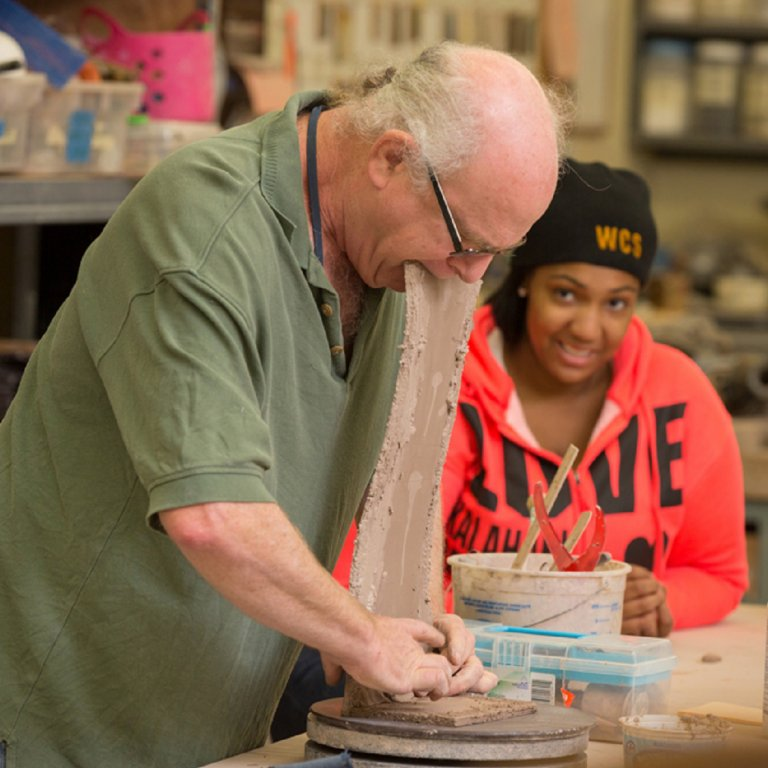 Steve Glazer, ceramics instructor, demonstrates clay forming as student watches.