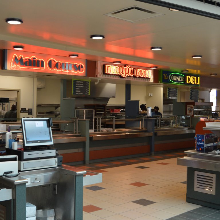 Interior of Skylight Cafe showing many food stations with neon lit signs.