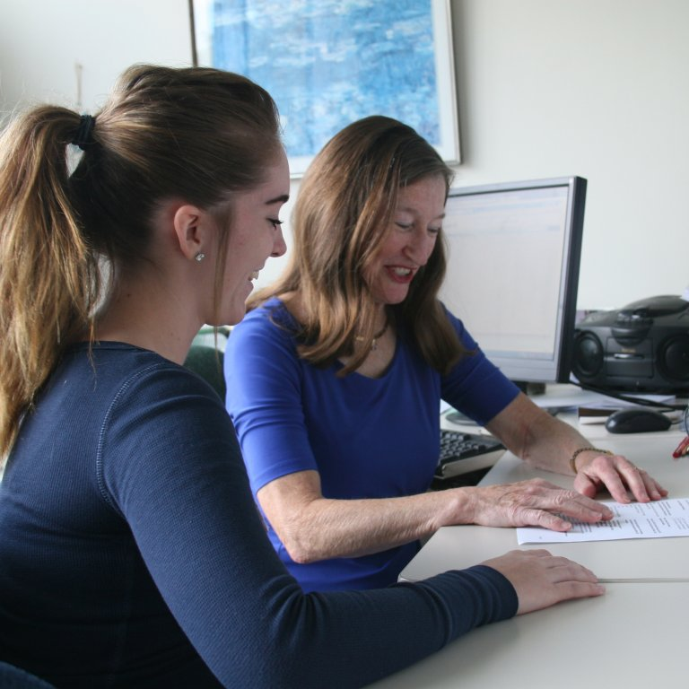 Counselor and student sit at a desk reviewing student's academic progress.