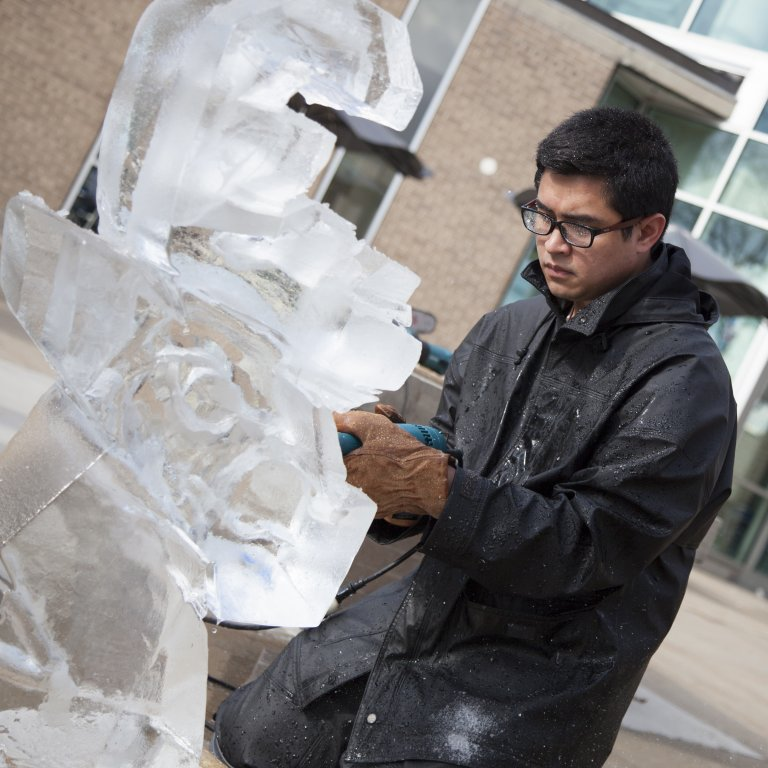 Ice carving student in a heavy coat and gloves carefully shapes ice block for upcoming competition.