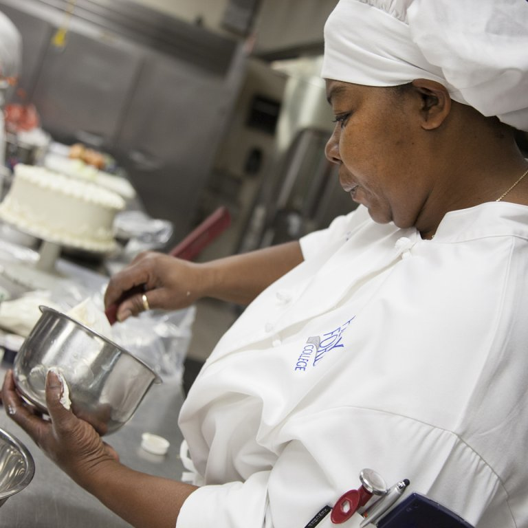 Student in chef's uniform, holding bowl and utensils.