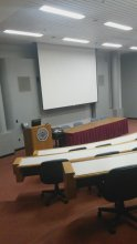 """Photograph of the inside of Berry Auditorium, rows of auditorium seating and a large projector screen are visible, as well as a wooden podium next to a table with chairs in the front of the room in view of the """"audience"""""""