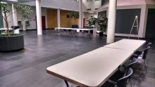 ASCC Atrium room L-111 pictured with tables and decorative plants; the room is large and has slate gray tiles, several white columns, and provides access to building exits and other rooms