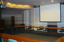 Photograph of Ghafari Conference room showing extended projection screen and chairs arranged around tables