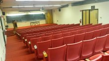 Photograph of the Liberal Arts Auditorium, containing rows of red seats with attached writing surfaces