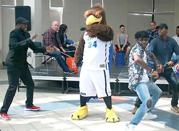 Hawkster and students dancing