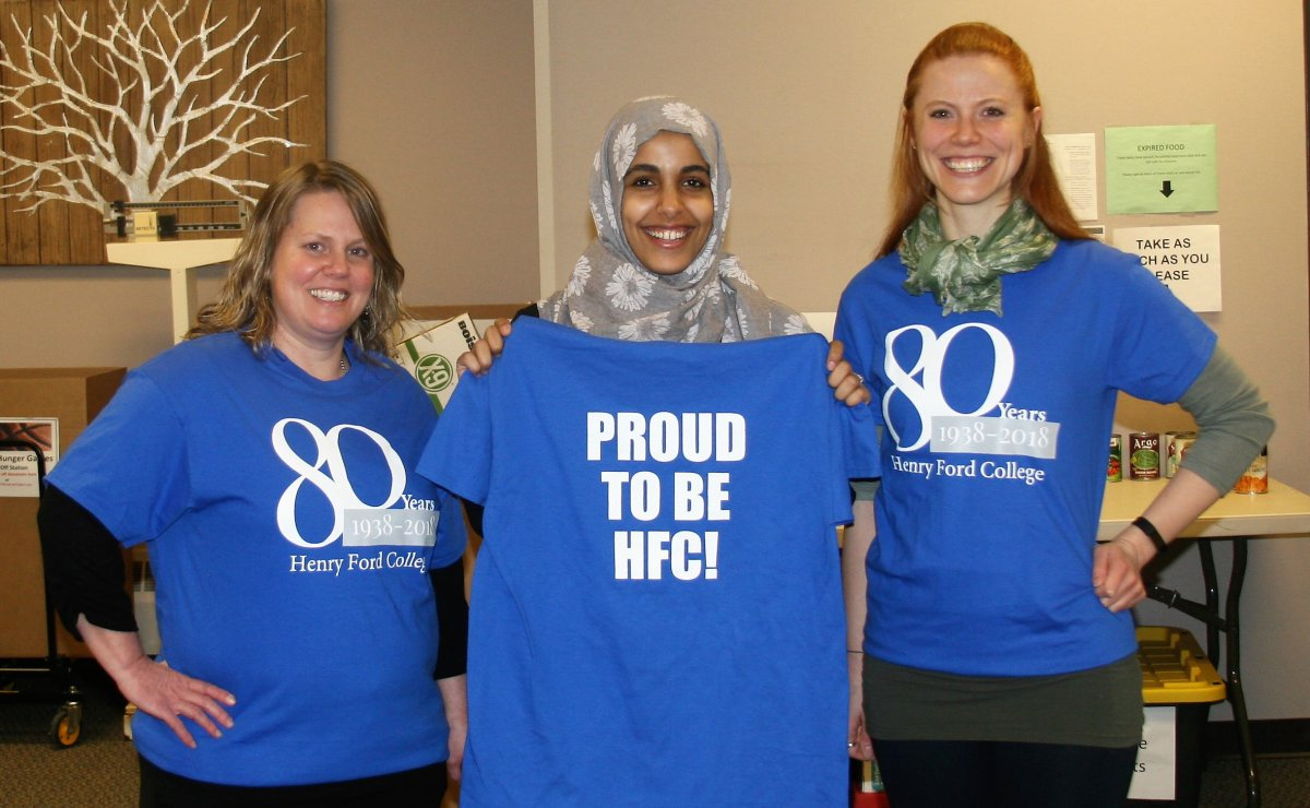 Group shot of 3 women modeling the HFC 80th anniversary T-shirt