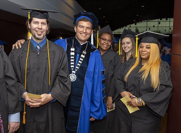 Five people in graduation regalia